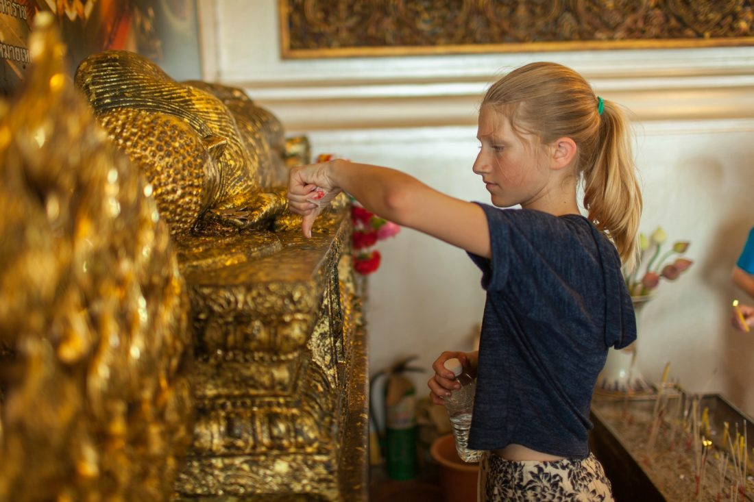Placing a gold leaf on Buddha