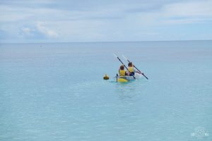 Kayaking and admiring the Great Barrier Reef below the surface of the clear kayak